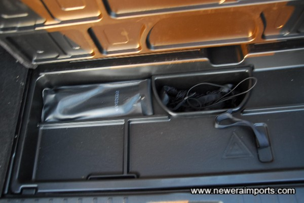 Tray for storage beneath luggage area.