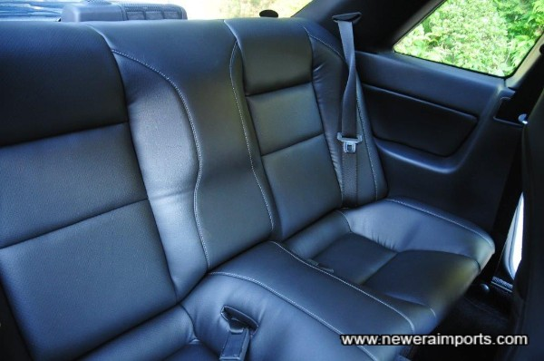 Rear seats are vinyl, but you'd be hard pressed to tell the difference against leather. Stitching is the same as on front seats.