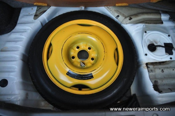 Spare wheel is unused. Tool kit in pouch next to wheel.